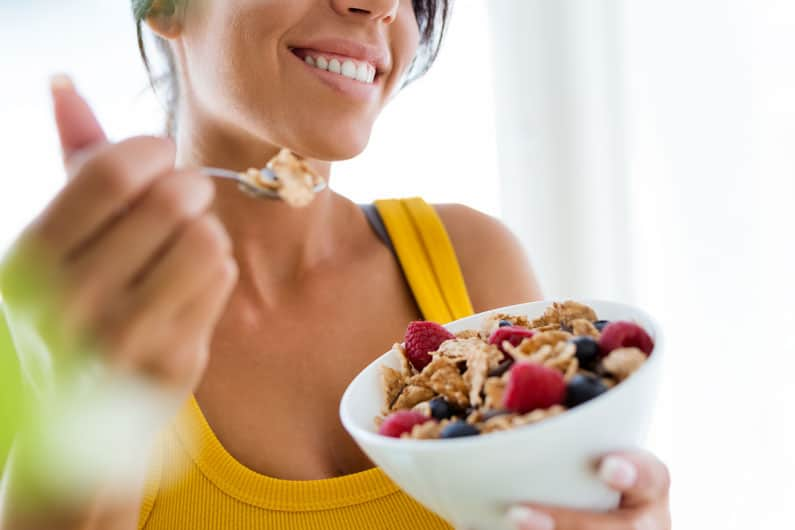 Beautiful young woman eats granola
