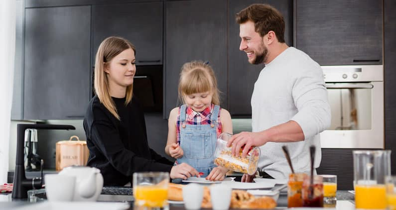 Girl with parents preparing breakfast