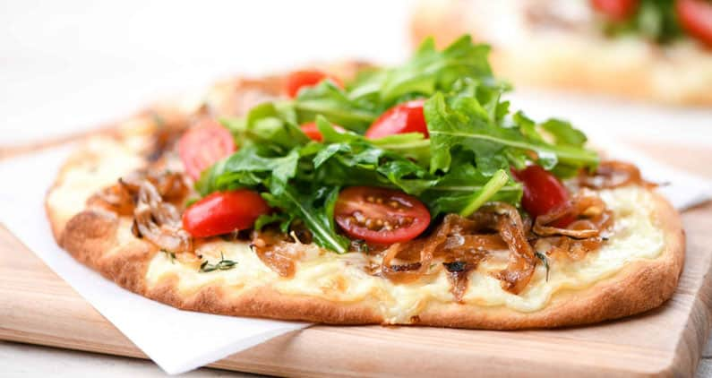 Healthy pizza on a wooden chopping board