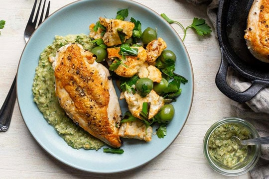 A nicely garnished dish of Roast Chicken with Green Romesco and Spiced Cauliflower