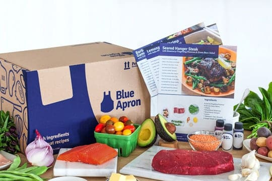 Blue Apron box with recipe pamphlets, salmon, meat and vegetables