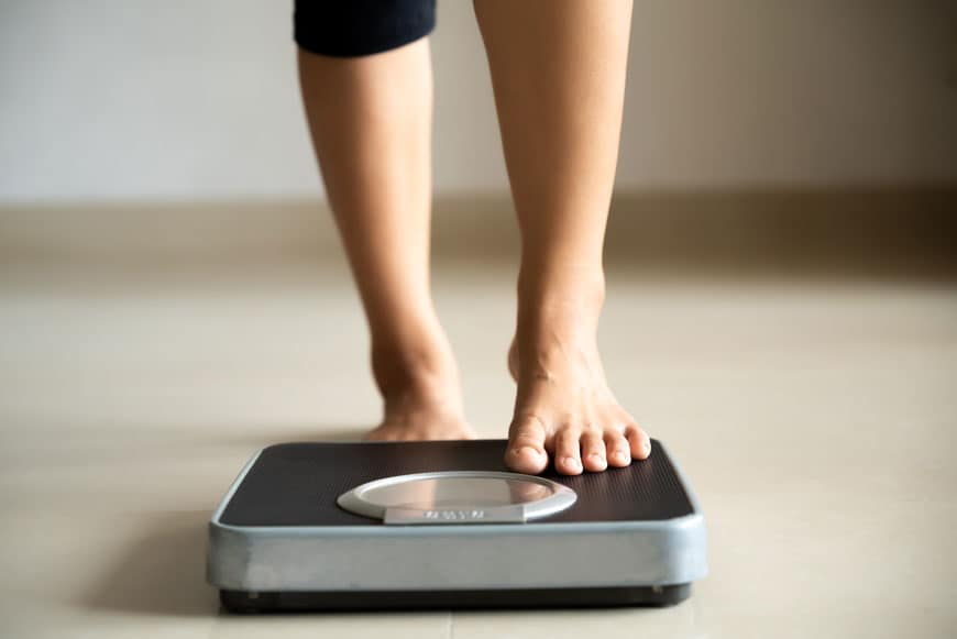 image of female leg stepping on the weigh scales