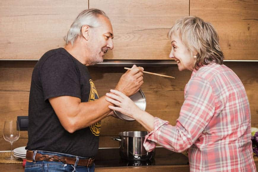 image of senior couple making dinner