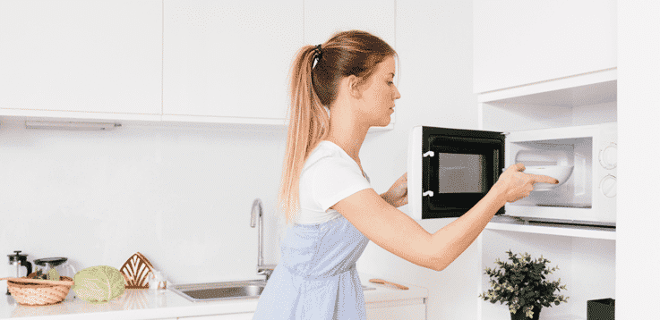 image of woman inserting food in microwave